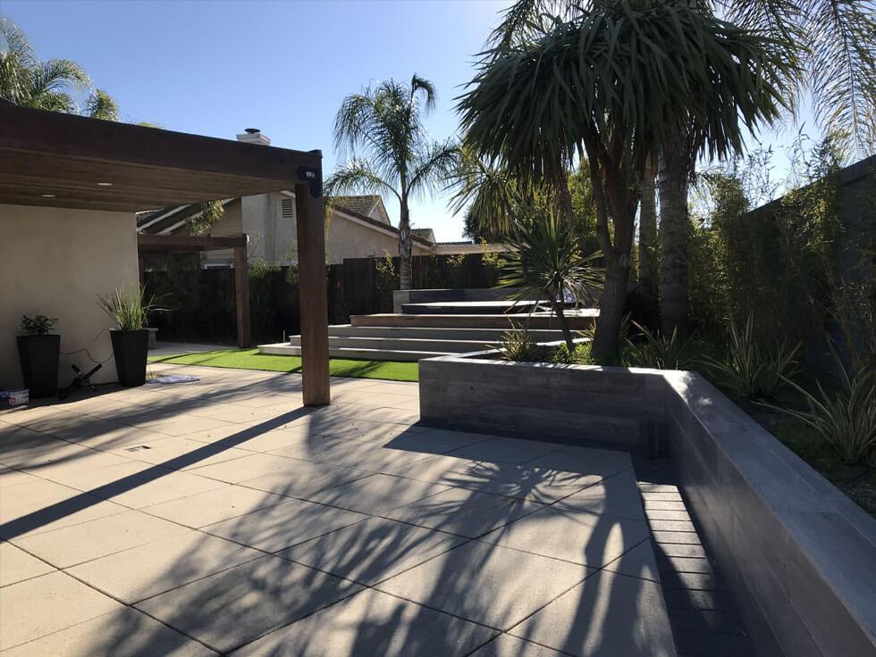 Modern backyard with Paseo II pavers and custom planter wall with tile facing